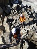 Den berghandboken och klienten får klara att klättra en stege till utgången av deras klättringrutt i Chamonix nära Mont Blanc royaltyfri bild