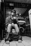 Den berusade mannen sitter i en toalett med en flaska av whisky Arkivbilder