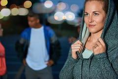 Den beslutsamma och sandiga millennial flickan under en genomkörare i ett stads- parkerar utomhus sen afton med hennes vänner Royaltyfri Bild