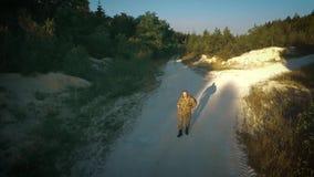 Den bestämda militära mannen går på den sandiga vägen stock video