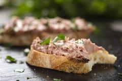 Den bet leverkorvsmörgåsen med huggen av persilja på ett mörker kritiserar royaltyfri fotografi