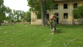 Den beväpnade closeupen av militären tjäna som soldat under utbildning som övar i bildande, medan ta över byggande stock video