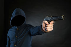 Den beväpnade personen i en hoodie pekar en handeldvapen på målet royaltyfri bild