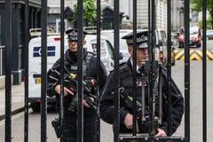 Den beväpnade polisen bevakar portarna in i Downing Street i Westminster, London Royaltyfria Bilder