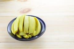 Den bevarade mango bär frukt i svart bunke Arkivfoto