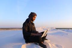 Den bildade arabiska studenten använder bärbara datorn och arbetar sammanträde på sand under Arkivbild
