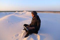 Den bildade arabiska studenten använder bärbara datorn och arbetar sammanträde på sand under Fotografering för Bildbyråer