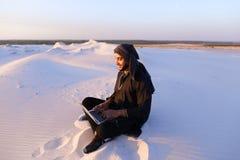 Den bildade arabiska studenten använder bärbara datorn och arbetar sammanträde på sand under Arkivbilder