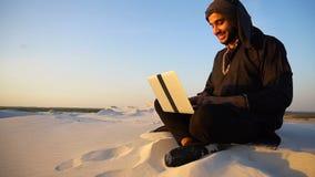 Den bildade arabiska studenten använder bärbara datorn och arbetar sammanträde på sand under sanddyn av öknen på varm sommarafton arkivfilmer