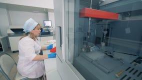 Den Biochemical analysatorn testar prövkopior, och en kvinnlig arbetare kontrollerar processen stock video