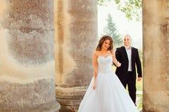 Den bländande bruden leder hennes man bland gamla pelare Fotografering för Bildbyråer