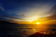 Den bländande ljusa solnedgången över ett tropiskt hav Arkivbild