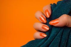 Den blänkte apelsinen spikar manikyr royaltyfri fotografi