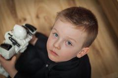 Den blåögda pojken som ser upp på trägolv med en robot i Royaltyfri Foto