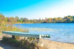 Den blåa bänken som förbiser en sjö i en kanadensare, parkerar Rum för kopieringsutrymme, ideal för en bok eller annonsering mini arkivfoto
