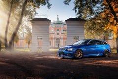Den blåa bilen BMW 3 serie E91 som står near höst, parkerar skogen Arkivfoton