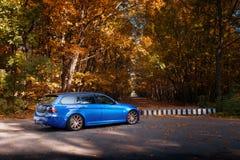 Den blåa bilen BMW 3 serie E91 som står near höst, parkerar skogen Arkivbild