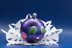 Den blåa bollen med den målade roliga framsidan lokaliseras på ett snöflingasnitt Royaltyfria Bilder