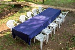 Den blåa bordduken med vit stol ordnar naturligt Arkivfoton