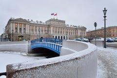 Den blåa bron på den Moika floden och ZAKSEN av SPb i vintern Arkivfoto