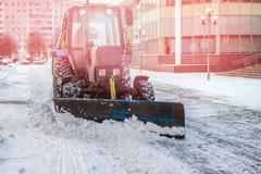 Den blåa bulldozern gör ren gatorna efter ett tungt naturligt snöfall jul som får klar Solig frostig dag royaltyfri foto
