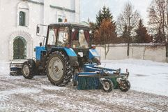 Den blåa bulldozern gör ren gatorna efter ett tungt naturligt snöfall jul som får klar Solig frostig dag close arkivbild