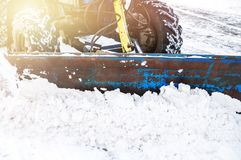 Den blåa bulldozern gör ren gatorna efter ett tungt naturligt snöfall jul som får klar Solig frostig dag close arkivfoton