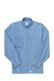 Den blåa denimskjortan isoleras på white royaltyfria foton