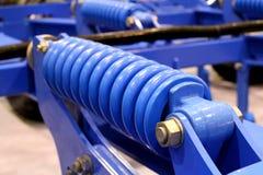 Den blåa detaljen av vårstötdämparen är en beståndsdel för mekanisk transport royaltyfri foto