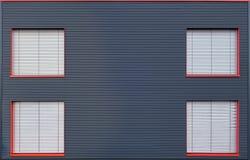 Den blåa fasaden för korrugerat järn med fyra stängde fönster Arkivfoto