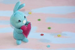 Den blåa gulliga kaninen med en röd hjärta i dess tafsar på ett rosa ljus - blå bakgrund handwork royaltyfria foton