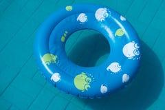 Den blåa gummicirkeln ligger i pölen i trädgården Begreppet av sommar arkivfoton