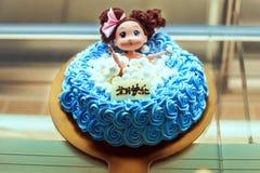 Den blåa härliga kakan dekorerade med en docka i badrummet Arkivfoto