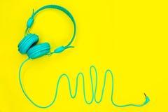 Den blåa hörlurar ligger på en färgrik gul bakgrund med kopieringsutrymme arkivfoto