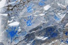 Den blåa handen skrivar ut på den metalliska glänsande stenväggen Royaltyfria Foton
