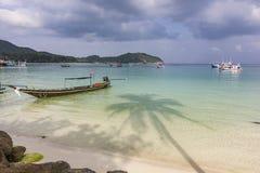 Den blåa havstranden med fartyg och skugga av gömma i handflatan på vatten i den phangan ön fotografering för bildbyråer