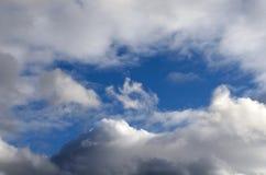 Den blåa himlen täckas av moln av olika former och format Royaltyfri Foto