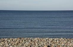 Den blåa horisonten som den pebbled stranden och ser möte himlen royaltyfria bilder