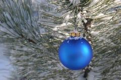 den blåa julprydnaden sörjer den snöig treen Arkivfoto