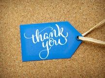 Den blåa klistermärkeförsäljningen på korkbakgrunden och text tackar dig Attraktion för kalligrafibokstäverhand Royaltyfri Foto