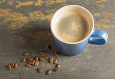 Den blåa koppen kaffe kritiserar på med bönor Royaltyfri Fotografi