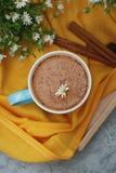 Den blåa koppen kaffe mjölkar den lekmanna- Buquet för blomman för kamomill för den träför bakgrund för kanelbruna pinnar för Lat royaltyfria bilder
