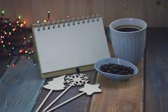 Den blåa koppen och anteckningsboken på jul tablen Royaltyfria Bilder