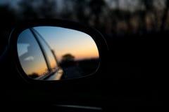 Den blåa landskapsolnedgången reflekterar i spegel av bilen arkivfoto
