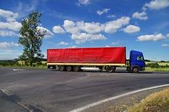 Den blåa lastbilen med rött seglar att passera tvärgator i bygden Arkivfoto