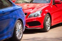 Den blåa och röda bilen är i parkeringsplatsnärbilden royaltyfri foto