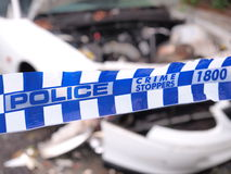 Den blåa och vita polisen tejpar cordoning av ett område med dåligt en skadad vit bil för olycka Arkivbild