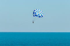 Den blåa parasailvingen drog vid ett fartyg i havsvattnet, Parasailin Royaltyfri Bild