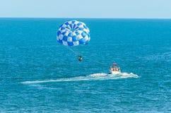 Den blåa parasailvingen drog vid ett fartyg i havsvattnet, Parasailin Royaltyfri Foto