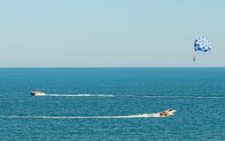 Den blåa parasailvingen drog vid ett fartyg i havsvattnet, Parasailin Royaltyfri Fotografi